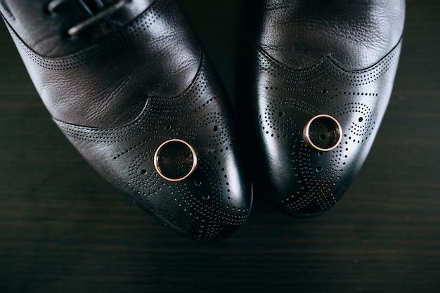 Anelli di nozze d'oro su scarpe di cuoio