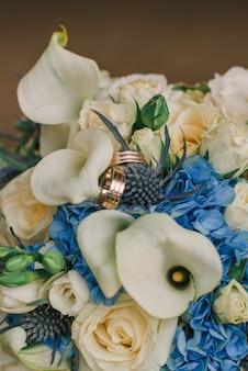 Anelli di oro di fidanzamento sui fiori di nozze con il fuoco selettivo
