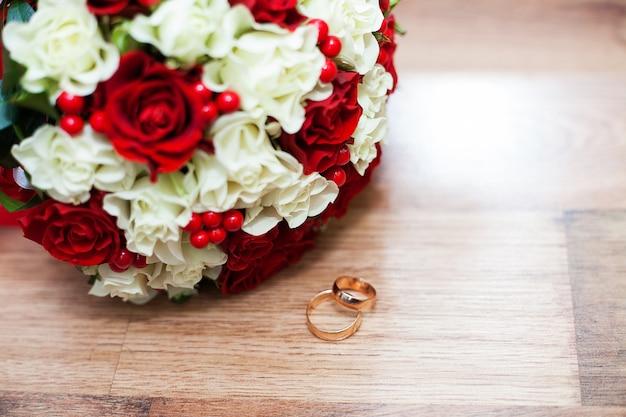 Anelli e un mazzo di nozze delle rose rosse e bianche sulla tavola