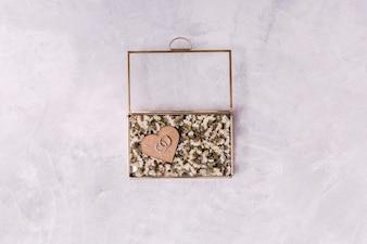 Anelli nel cuore dell'ornamento fra i fiori in scatola