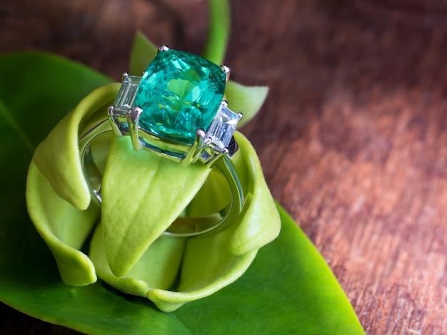 Anello con gemma verde con usura in diamante bianco con petali di fiore ylang-ylang