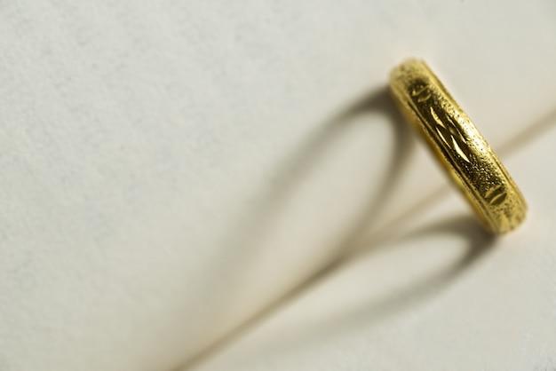 Anello d'oro con ombra a forma di cuore sulla pagina del libro