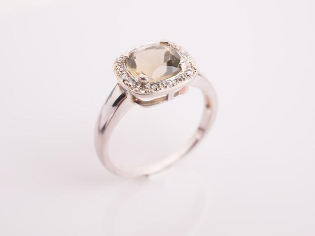 Anello della pietra preziosa sul tavolo bianco