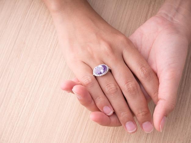 Anello della pietra preziosa sulla mano della donna