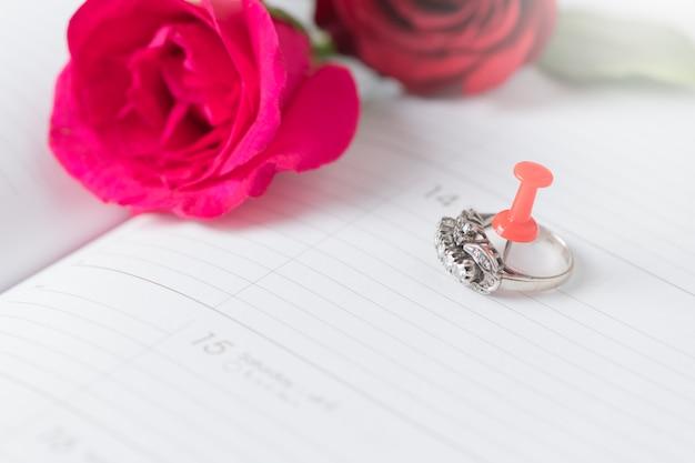 Anello di diamanti sul calendario con rosa rosa, amore e concetto di san valentino
