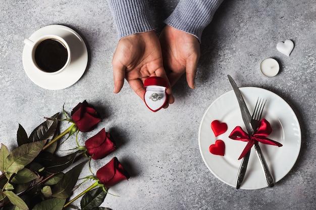 Anello di fidanzamento della tenuta della mano dell'uomo della regolazione della tavola di cena romantica di giorno di biglietti di s. valentino