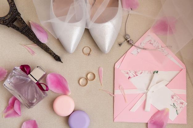 Anello di fidanzamento, due fedi nuziali vicino a scarpe da sposa su tacchi alti, bottiglia di profumo, invito, gioielli per la sposa con statuetta della torre eiffel e petali di rosa