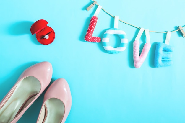Anello di fidanzamento e accessori della sposa su sfondo di colore blu, vista dall'alto. concetto di amore