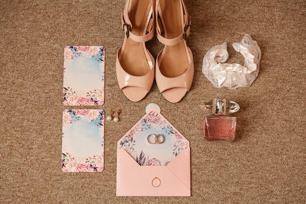 Anello di fidanzamento e due fedi nuziali su invito a nozze vicino a scarpe da sposa