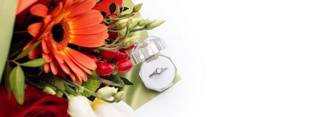 Anello di fidanzamento in confezione regalo con brillante mazzo di fiori. l'offerta di sposarsi. regalo per san valentino. proposta di matrimonio per la donna amata. simbolo di amore e matrimonio.