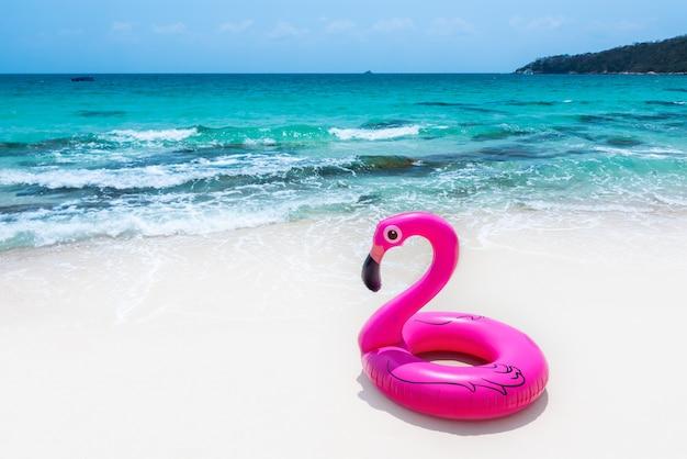 Anello di vita in gomma rosa sulla spiaggia.