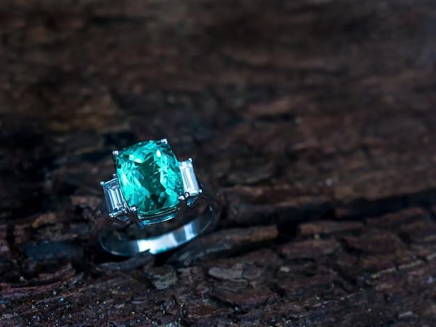 Anello gemma verde con diamante bianco su fondo in legno vecchio