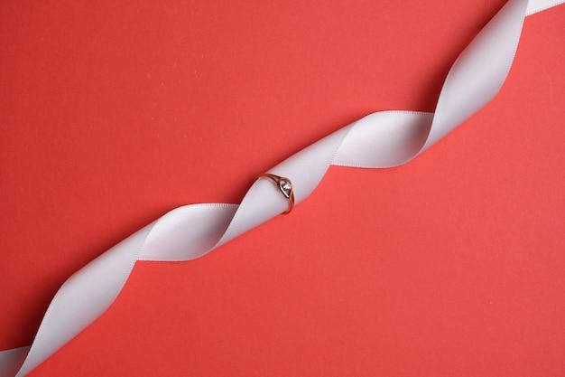 Anello in oro con un nastro bianco su uno spazio rosso. vista dall'alto.
