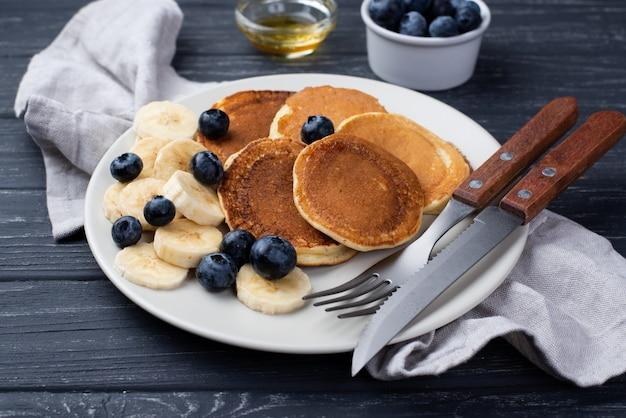 Angolo alto dei pancake della prima colazione sul piatto con i mirtilli e le fette della banana