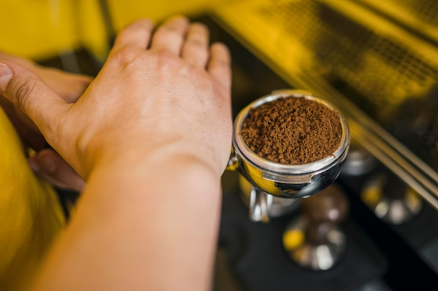 Angolo alto del barista che livella il livello del caffè per la tazza della macchina