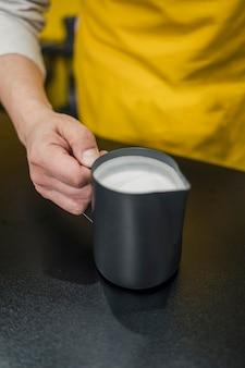 Angolo alto del barista che tiene tazza di latte