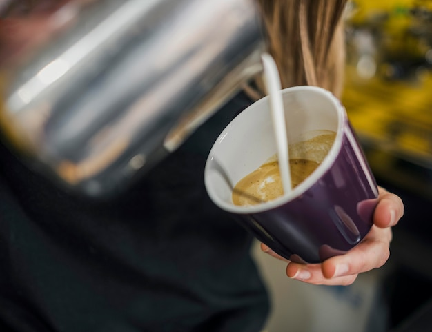 Angolo alto del barista femminile che versa latte nel caffè