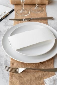 Angolo alto del piatto con carta vuota e posate