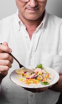 Angolo alto del piatto della tenuta dell'uomo con alimento sano