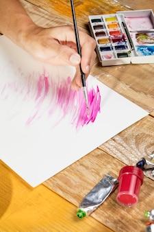 Angolo alto dell'artista con la pittura del pennello nello studio