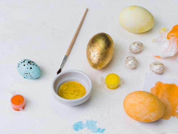 Angolo alto dell'uovo di pasqua dorato con la tintura e la spazzola