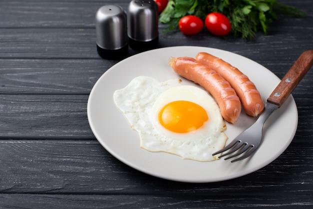 Angolo alto dell'uovo e delle salsiccie della prima colazione sul piatto con i pomodori e le erbe
