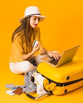 Angolo alto della carta di credito della tenuta della donna mentre lavorando al computer portatile