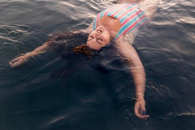 Angolo alto della donna che si rilassa nell'acqua alla spiaggia