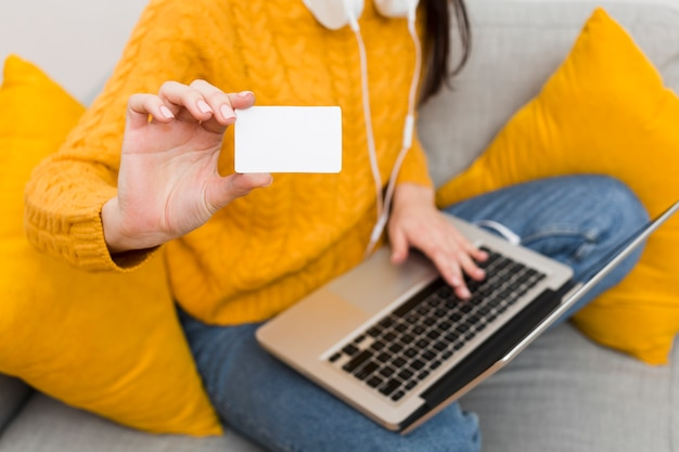 Angolo alto della donna con il computer portatile sul rivestimento che mostra la carta di credito