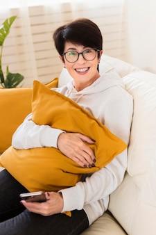 Angolo alto della donna di smiley sul sofà con lo smartphone