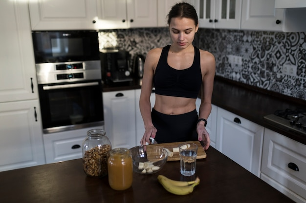 Angolo alto della donna sportiva che prepara pasto sano