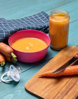 Angolo alto di alimenti per bambini in una ciotola con ciuccio e carote