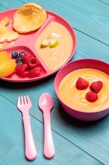 Angolo alto di alimenti per l'infanzia in una ciotola con assortimento di frutta
