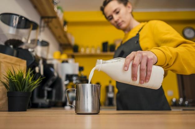 Angolo basso del barista che versa latte