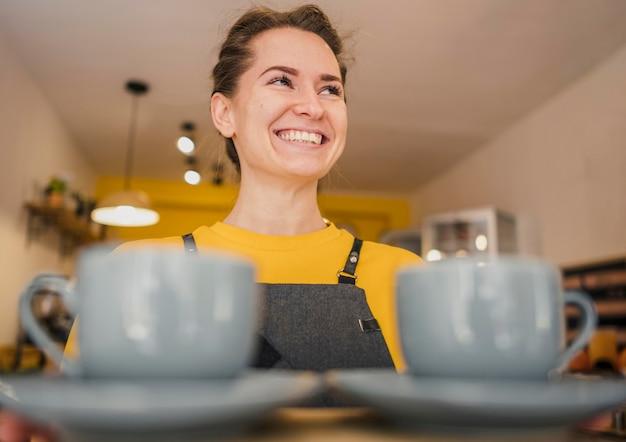 Angolo basso del barista di smiley che serve tazze di caffè