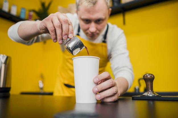 Angolo basso del barista versando il caffè