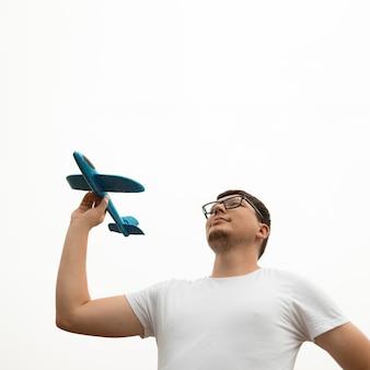 Angolo basso del giovane che tiene un aeroplano