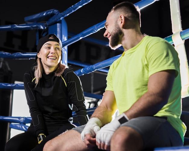 Angolo basso del pugile femminile e trainer maschio che hanno una conversazione accanto al ring