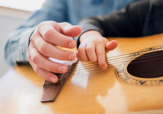 Angolo basso dell'insegnante e della chitarra della tenuta del bambino