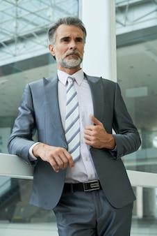 Angolo basso dell'uomo d'affari elegante che sta nell'edificio per uffici