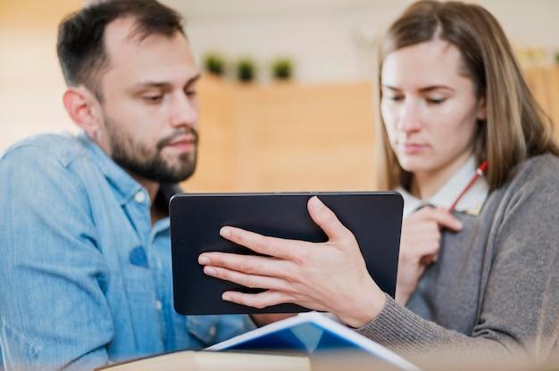 Angolo basso dell'uomo e della donna che impara a casa dalla compressa