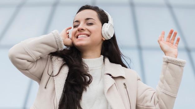Angolo basso della donna felice che ascolta la musica sulle cuffie