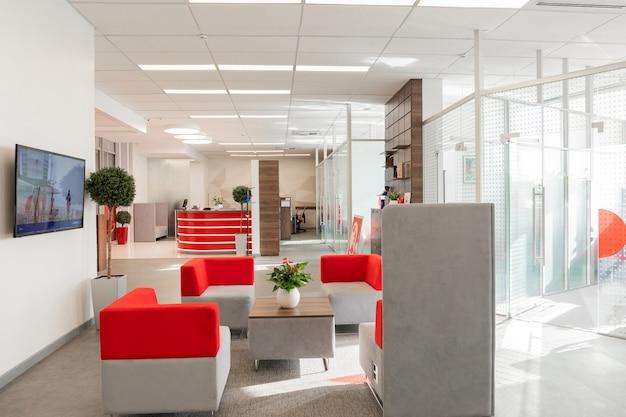 Angolo dell'ufficio moderno con pareti bianche, pavimento grigio, area open space con poltrone rosse e bianche e stanze dietro la parete di vetro