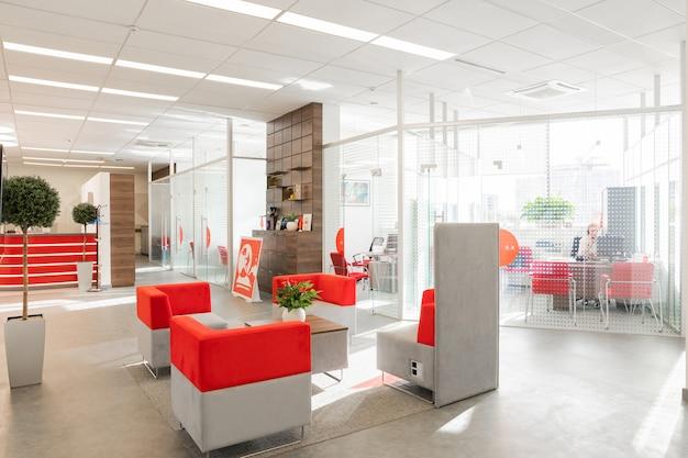 Angolo di ufficio moderno con pareti bianche, pavimento grigio, spazio all'aperto con poltrone rosso-bianco e stanze dietro la parete di vetro