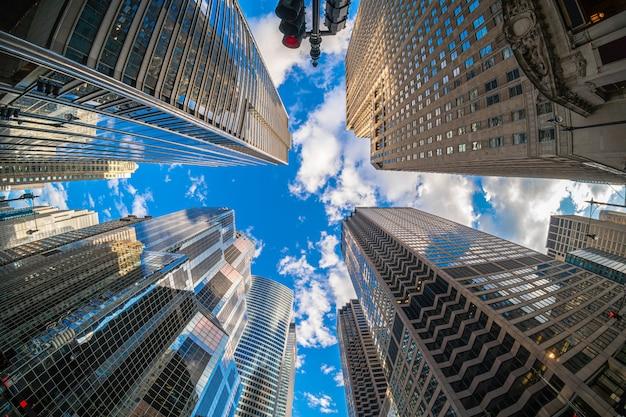 Angolo di uprisen con scena fisheye del centro di chicago grattacielo con riflesso di nuvole tra alti edifici che hanno l'aereo che vola sopra il cielo, illinois, stati uniti, affari e prospettiva