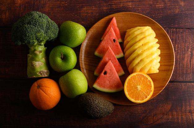 Anguria, ananas, arance, tagliate a pezzi con avocado, broccoli e mele sul tavolo di legno. vista dall'alto.