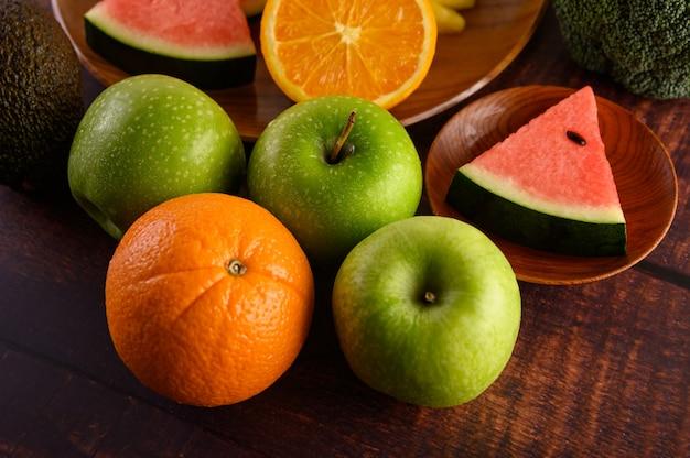 Anguria, arance, tagliate a pezzi con avocado e mele sul tavolo di legno.