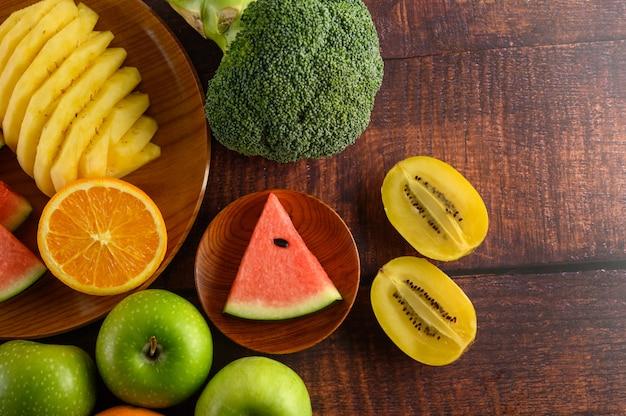 Anguria, arancia, ananas, kiwi tagliati a fette con mele e broccoli su un piatto di legno e un tavolo di legno.
