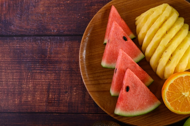 Anguria, arancia e ananas tagliati a pezzi su un piatto di legno