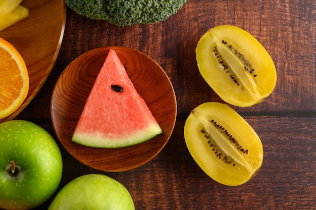 Anguria, arancia, kivi, tagliata a pezzi con mele e broccoli su un piatto di legno.